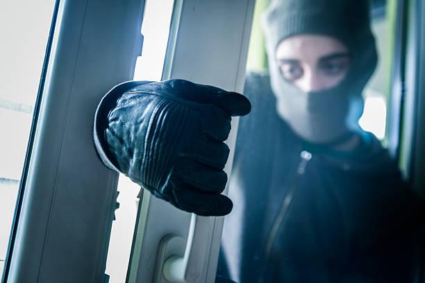Burglar Breaking Into House stock photo