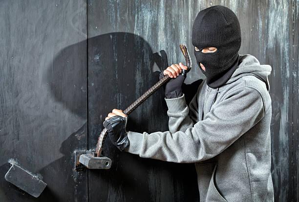 Burglar breaks lock on door stock photo