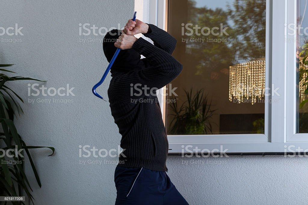 Burglar breaks the window stock photo