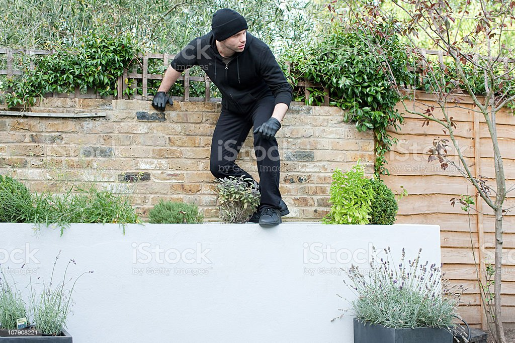 Burglar climbing on wall stock photo