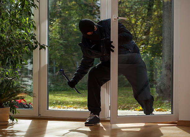 Burglar entering through the balcony window stock photo