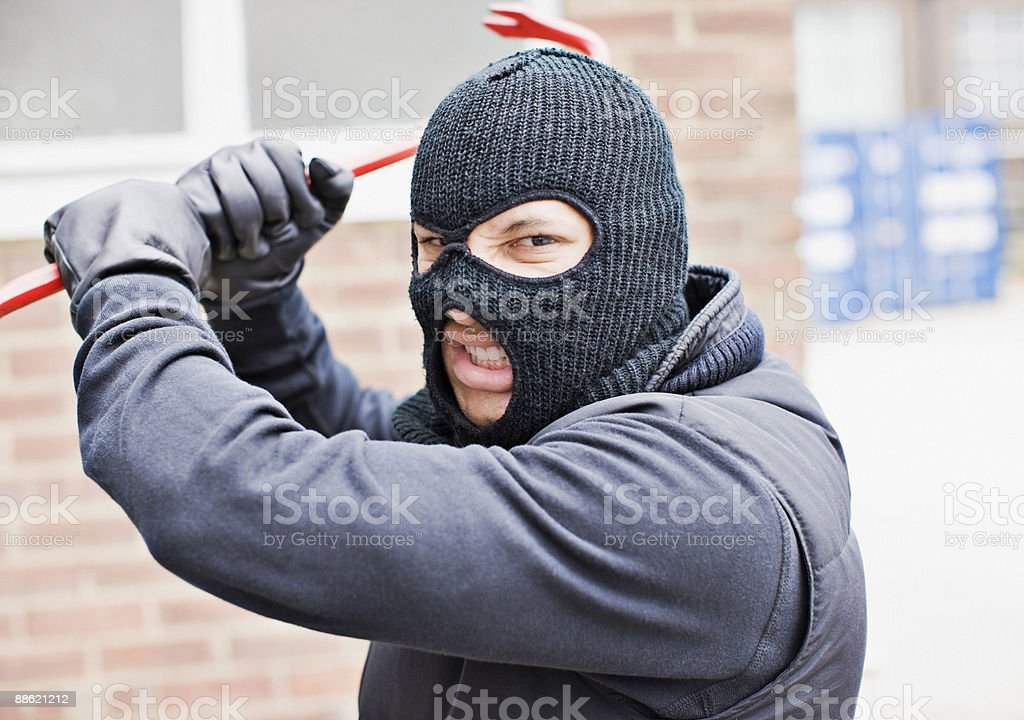 Burglar in ski mask wielding crowbar stock photo