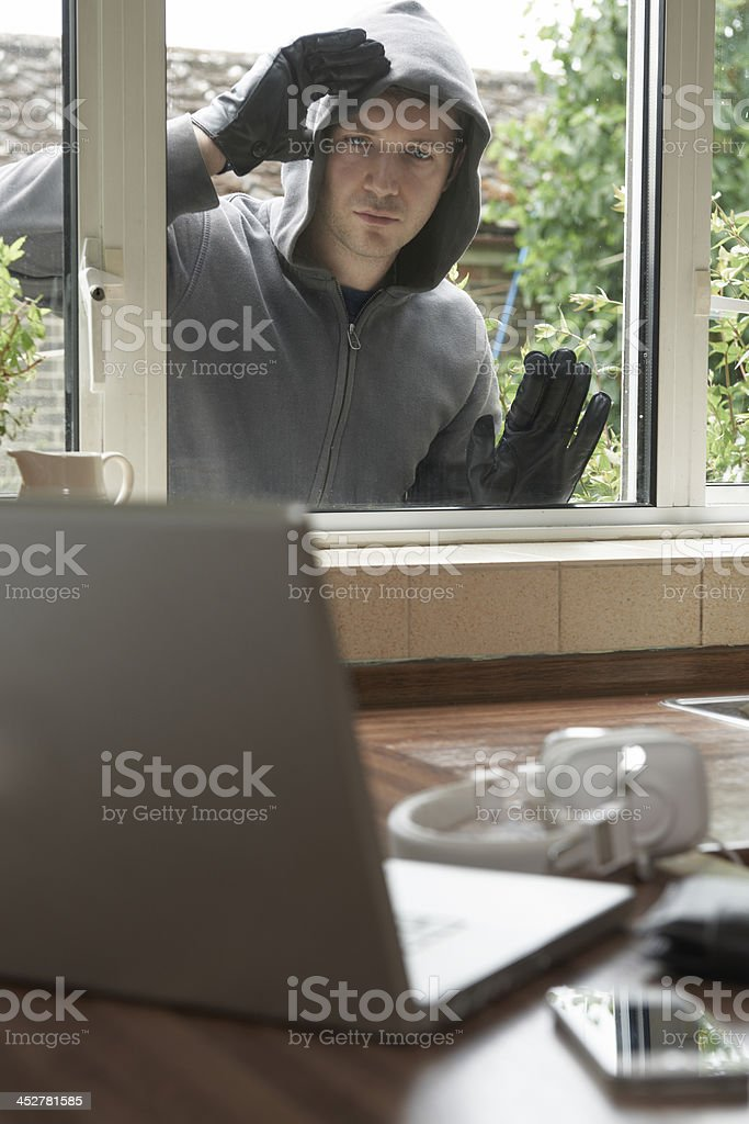 Burglar looking at electronics through house window royalty-free stock photo