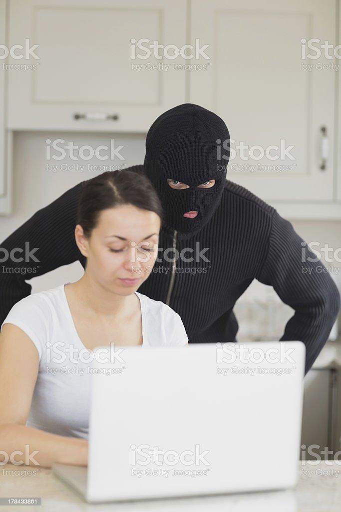 Burglar looking at the laptop behind woman royalty-free stock photo