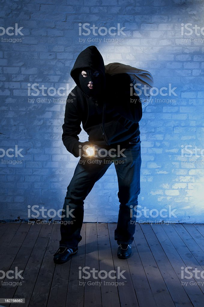Burglar on the move pointing flashlight royalty-free stock photo