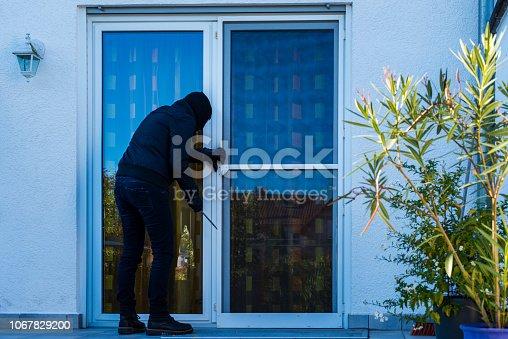 burglar opening backdoor of a house