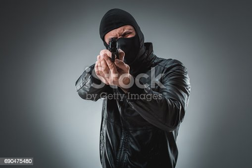 istock Burglar or terrorist in black mask shooting with gun 690475480
