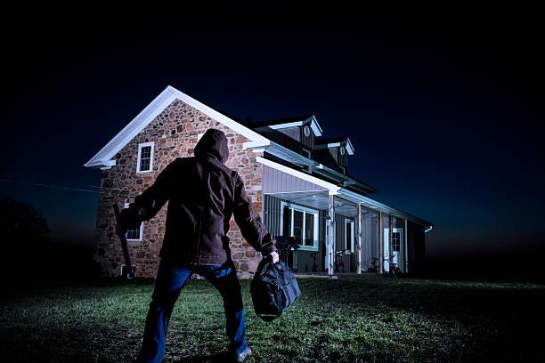 Burglar outside a house at night stock photo