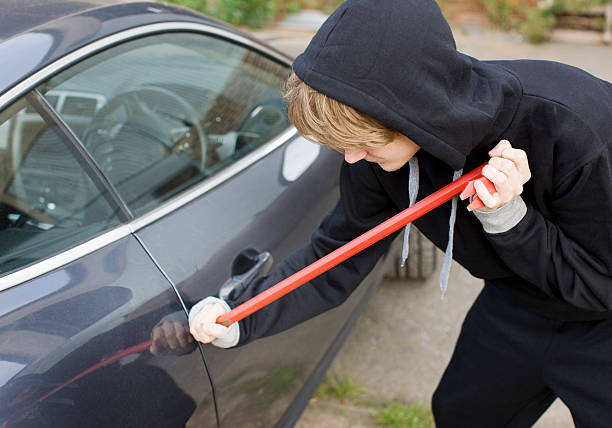 burglar prying car window open with crowbar - stealing crime stock photos and pictures