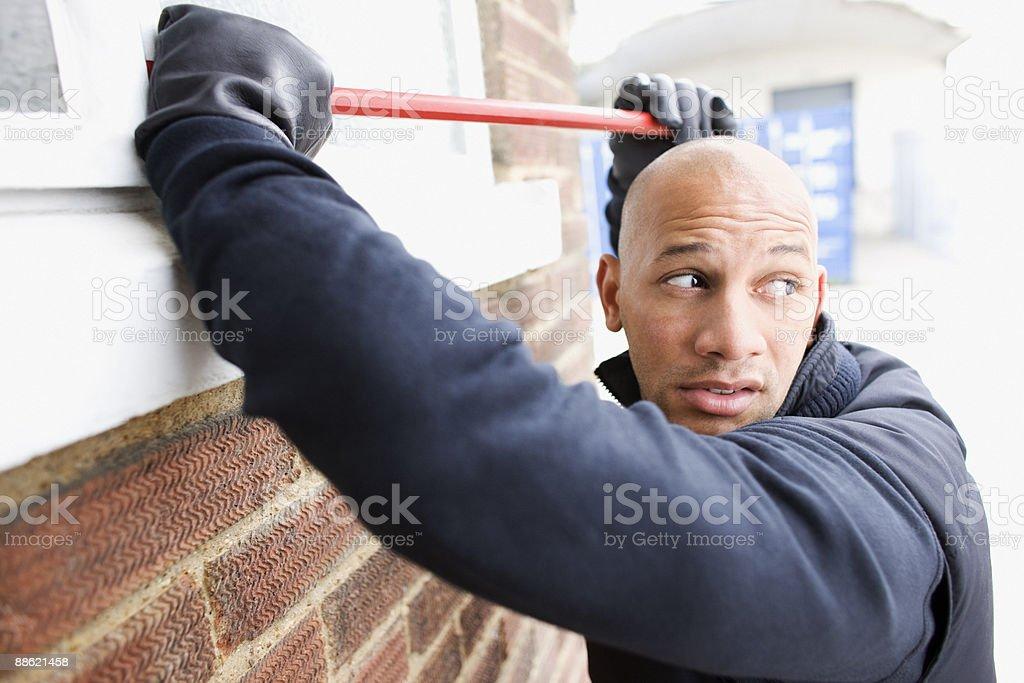 Burglar prying window open with crowbar royalty-free stock photo