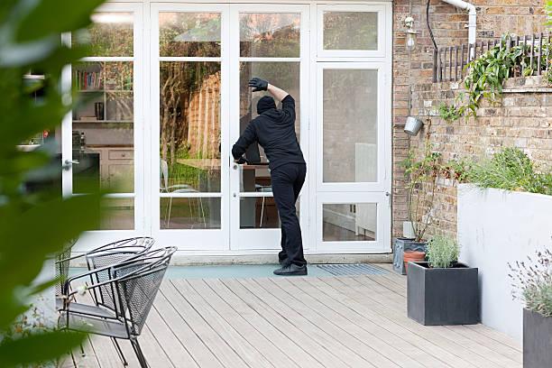 Burglar standing at patio door stock photo
