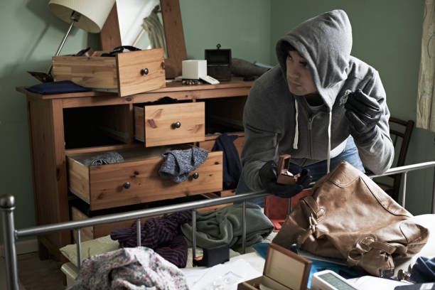 burglar stealing items from bedroom during hose break in - thief stock photos and pictures