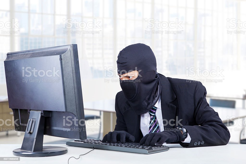 Burglar steals information on computer royalty-free stock photo