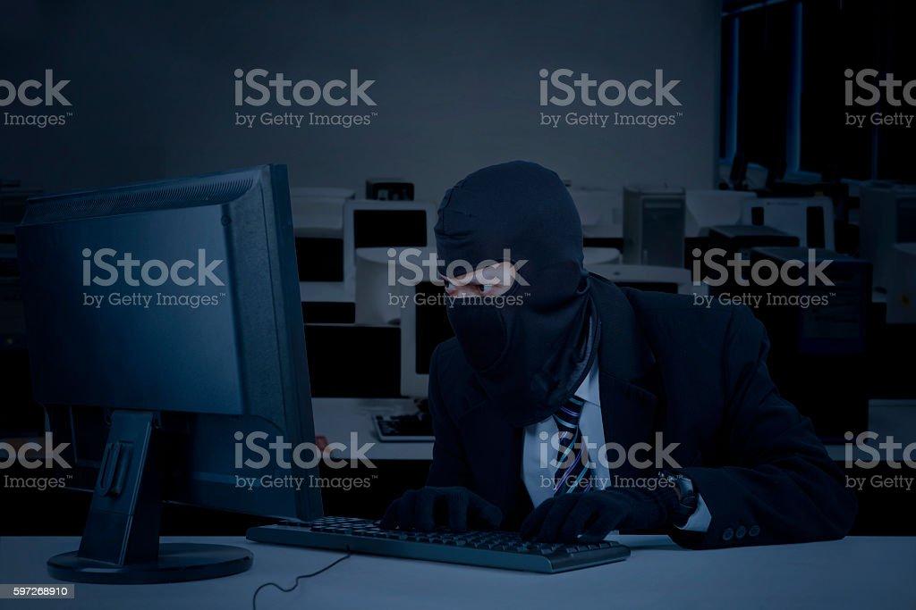 Burglar takes data on computer Lizenzfreies stock-foto