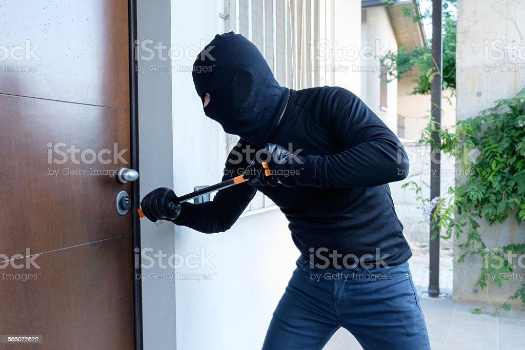 Burglar trying to force a door lock using a crowbar - Photo