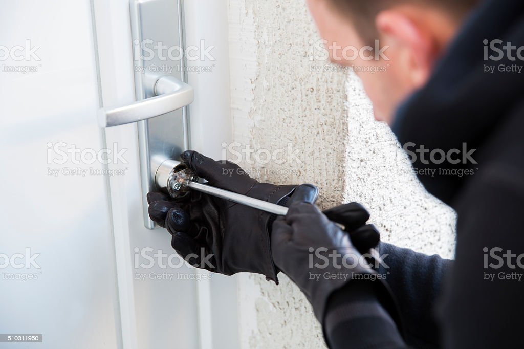 Burglar using special tools to break in  a house stock photo