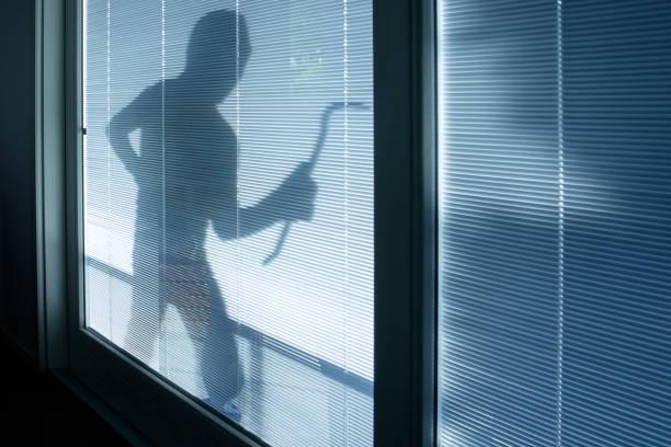 Burglar wearing a balaclava looking through house window stock photo