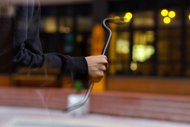 Burglar with a crowbar on the background of the shop. stock photo