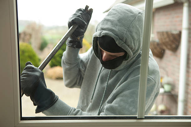 Burglar with crowbar trying to enter house, stealing valuables stock photo