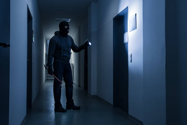 Burglar With Flashlight And Crowbar In Office Building stock photo