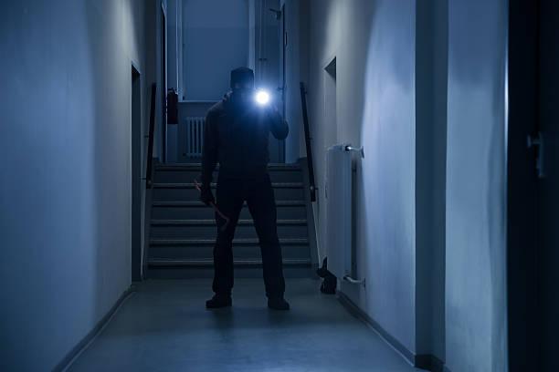 Burglar With Flashlight And Crowbar In Office Corridor stock photo