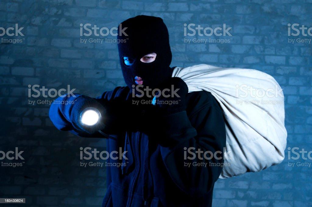 Burglar with sack and flashlight stock photo