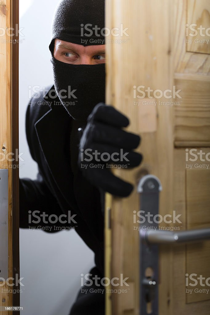 Burglary crime - burglar opening a door royalty-free stock photo