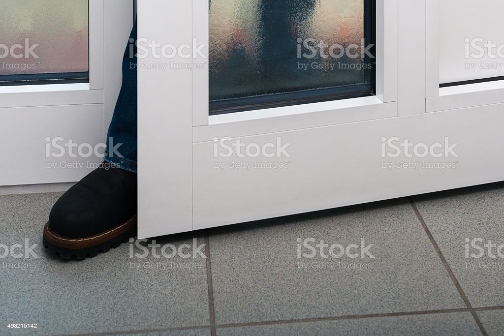 burgler with boot at  front door stock photo