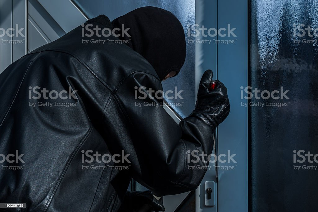 burgler with screwdriver at front door stock photo