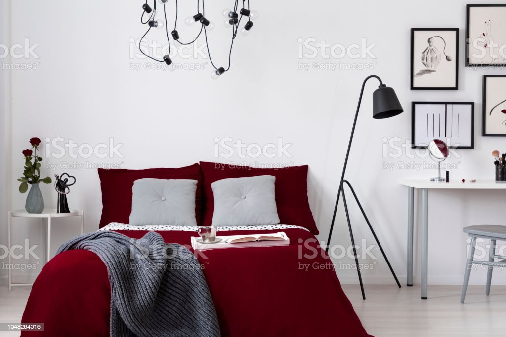 A burgundy bedding and gray pillows on a bed in a white wall bedroom...