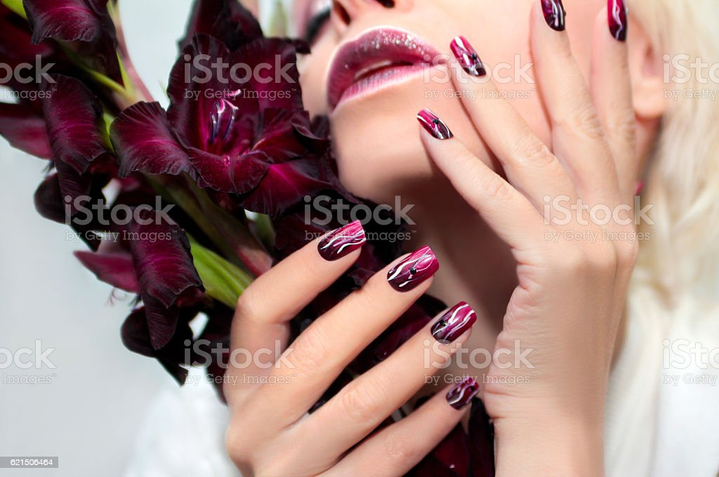 Burgundy manicure with gladiolus. foto stock royalty-free