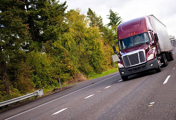 burgundy semi truck and reefer trailer in straight wide highway - aufgemotzte trucks stock-fotos und bilder