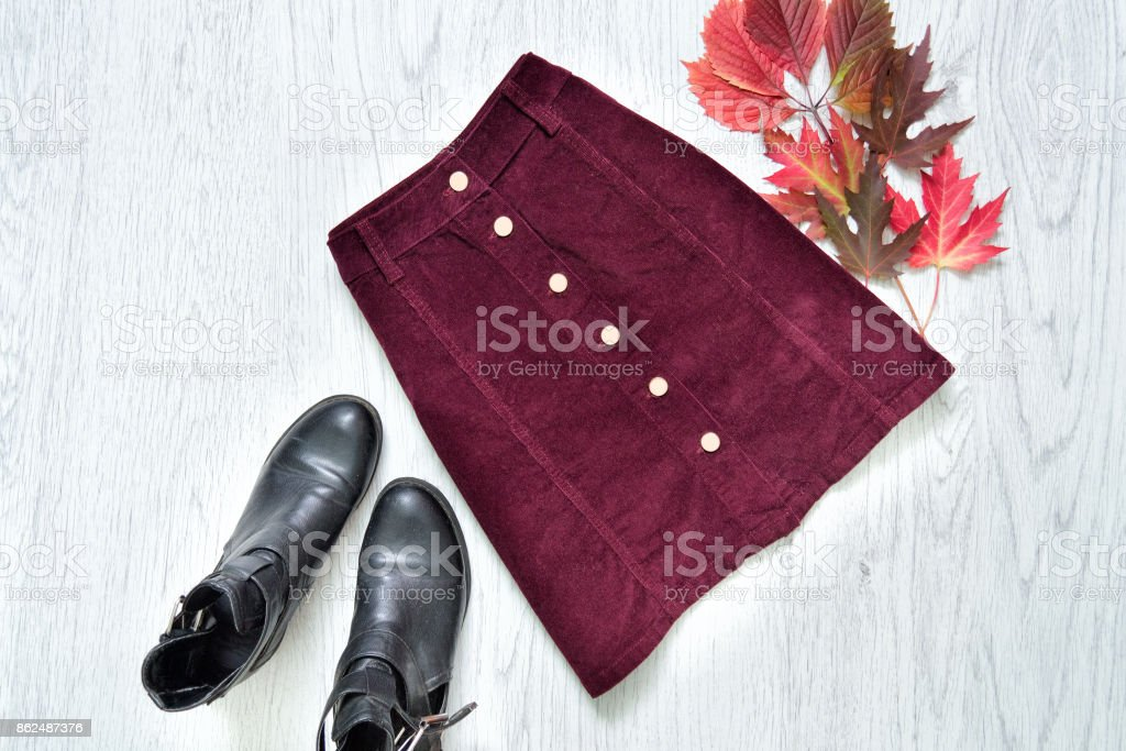 Burgundy suede skirt, black boots and red leaves. Fashionable concept. stock photo