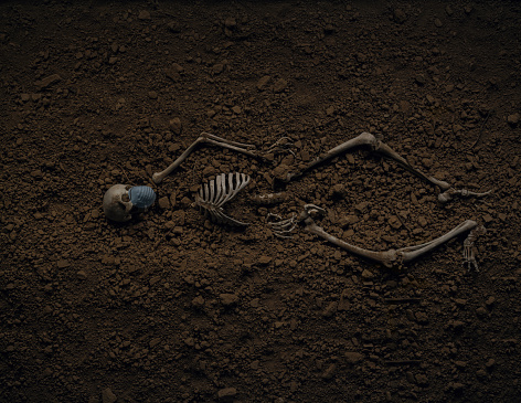 Skeleton of a victim buried. Mouth mask.