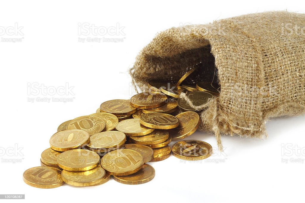 Burlap bag with gold coins spilling out stock photo