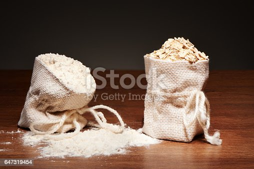 912671588istockphoto Burlap bags of flour and oatmeal flakes on dark table 647319454