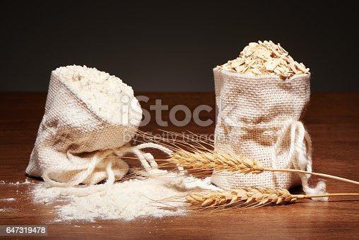 912671588istockphoto Burlap bags of flour and oatmeal, wheat ears on table 647319478