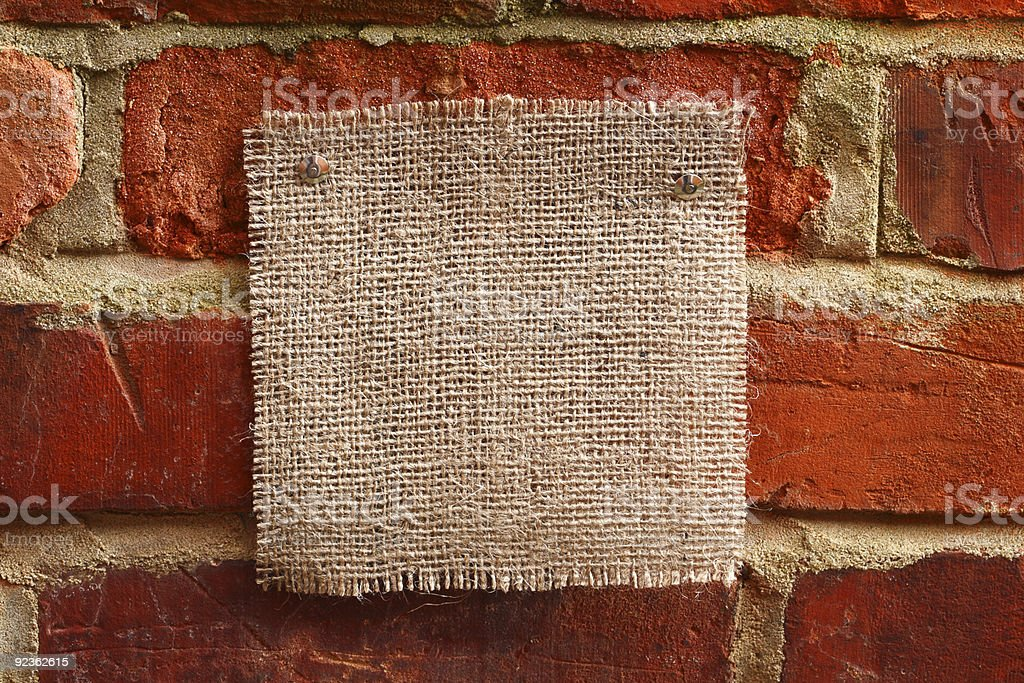 burlap canvas with lacerate edges on red old brick wall royalty-free stock photo