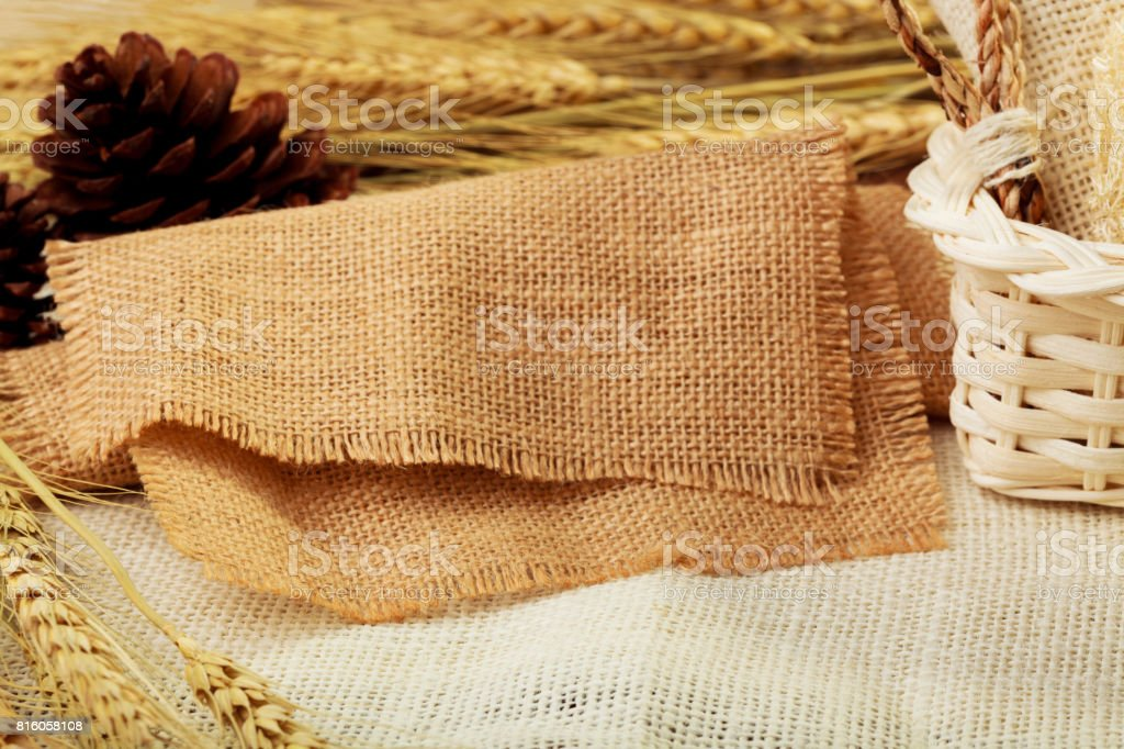 Burlap on table background. with pine cone, basket and oat blurry in the background stock photo