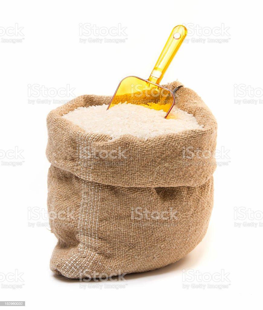 Saco de arpillera con una cuchara de arroz y plástico - foto de stock