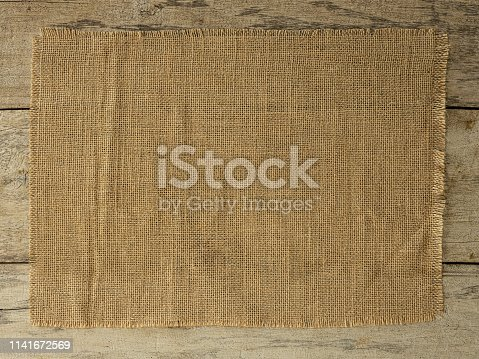 burlap sack material swatch sign space on an old wooded paneled board background. Textured and rustic with great copy space.