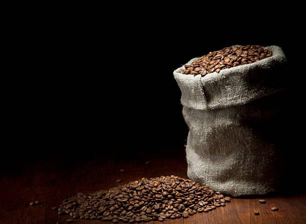 Jute sack Kaffeebohnen gegen Dunkles Holz Hintergrund – Foto