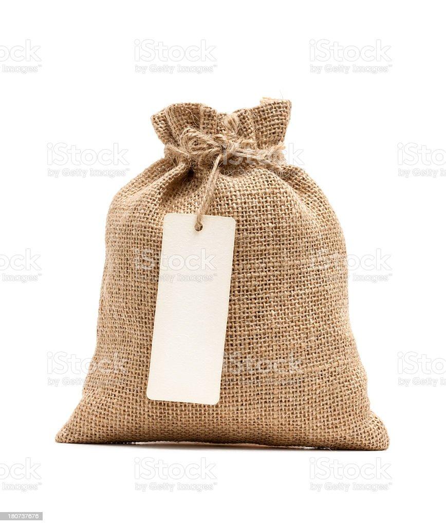 Burlap sack with blank label isolated on white background stock photo