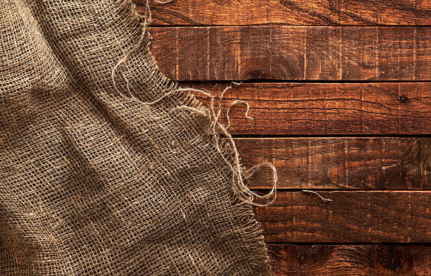 Burlap texture on wooden background Burlap texture on wooden table background. Wooden table with sacking burlap stock pictures, royalty-free photos & images