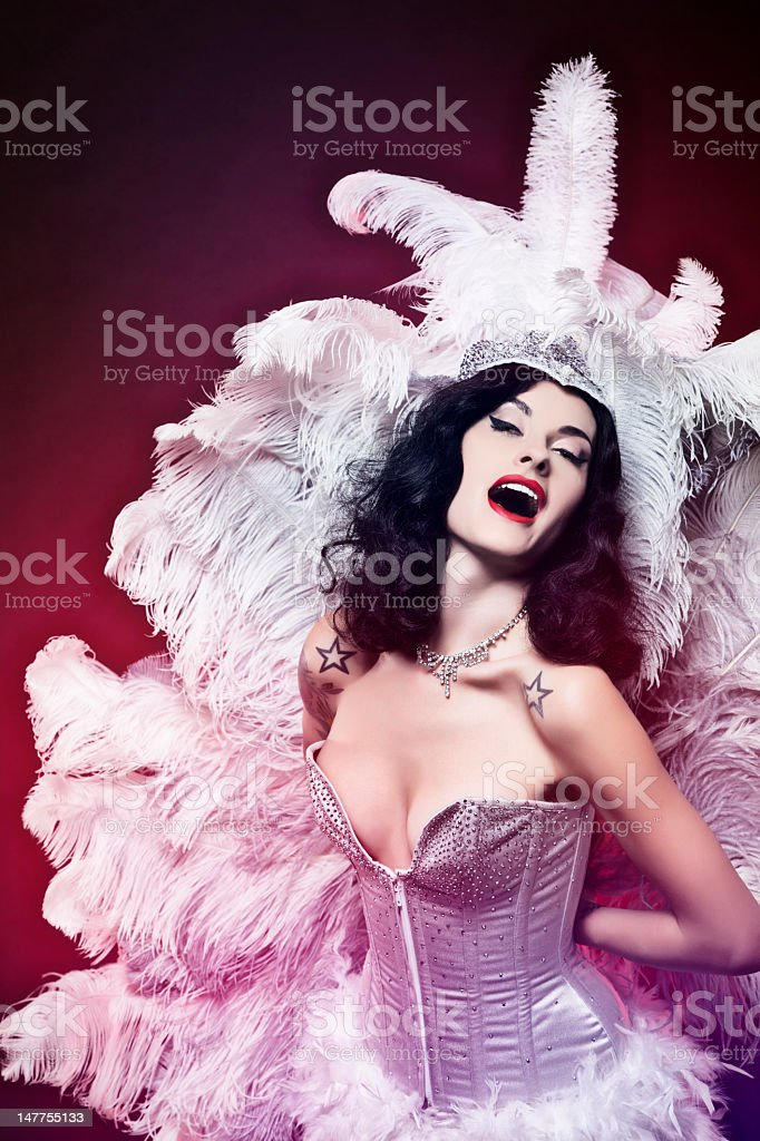 Burlesque woman in light purple on dark red background stock photo