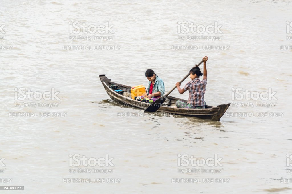 Burmese ladies crossing river by paddling a small boat stock photo