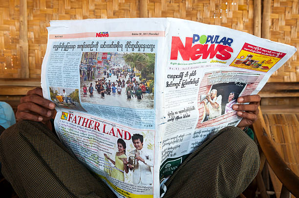 Reading the newspaper in Myanmar Inle Lake, Myanmar - November 6, 2011: A Burmese man reads the news in a Burmese-language newspaper at Inle Lake, Myanmar. Stories include news about Aung San Suu Kyi and flooding in Thailand. front page stock pictures, royalty-free photos & images
