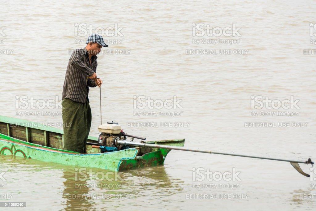 Burmese man starting the engine of homemade motor boat 1 stock photo