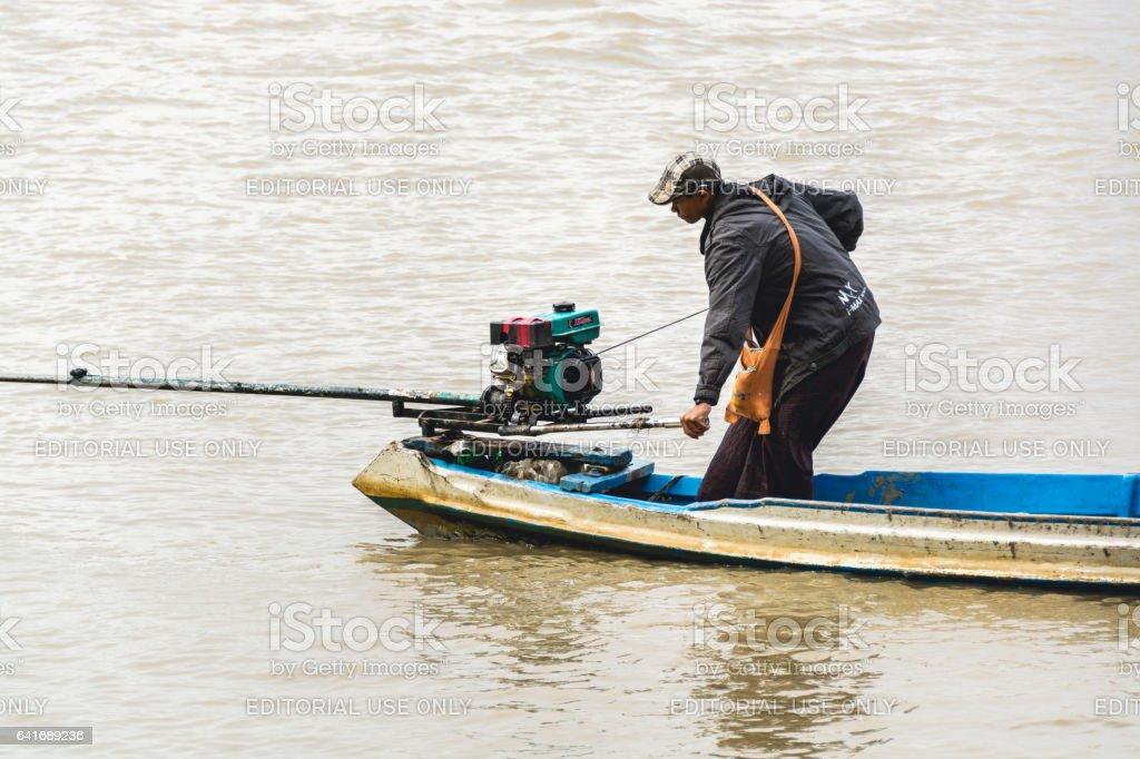 Burmese man starting the engine of homemade motor boat 3 stock photo