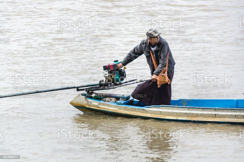 Burmese man starting the engine of homemade motor boat 4 stock photo